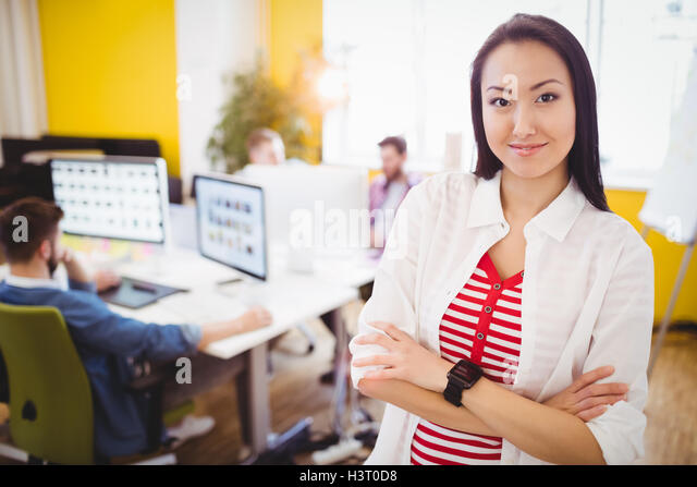 Portrait of beautiful executive standing at editing office - Stock Image