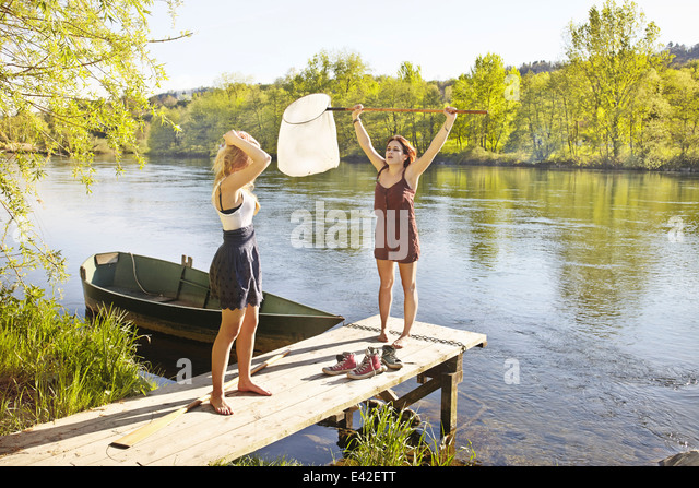 Young women standing on jetty, one holding fishing net - Stock Image