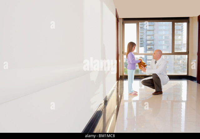 Doctor giving a stuffed toy to a girl - Stock Image