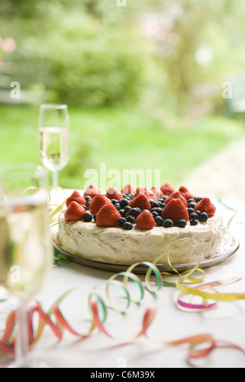 Strawberry blueberry cake and champagne on table decorated with party streamers - Stock Image