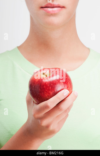 Close-up of a woman holding a red apple - Stock-Bilder