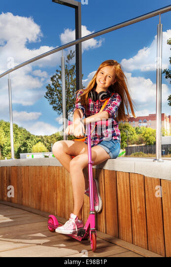 Positive girl with leg on scooter sitting in park - Stock Image
