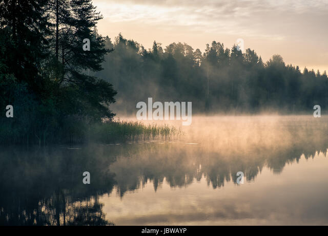 Scenic landscape with lake and sunrise at morning in Finland - Stock Image