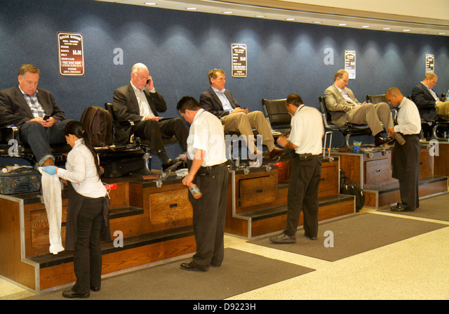 Texas Houston George Bush Intercontinental Airport IAH concourse gate area shoe shine service man customers - Stock Image