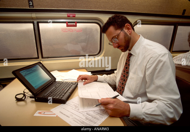 New Jersey Princeton Amtrak train commuter passenger computer laptop man work notebook - Stock Image
