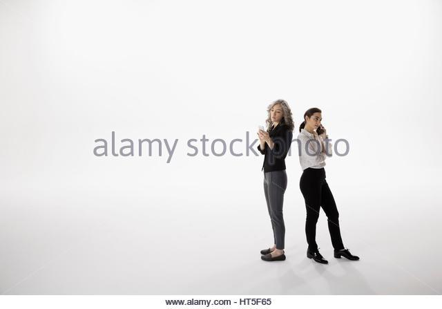 Businesswomen talk on cell phone and texting against white background - Stock-Bilder