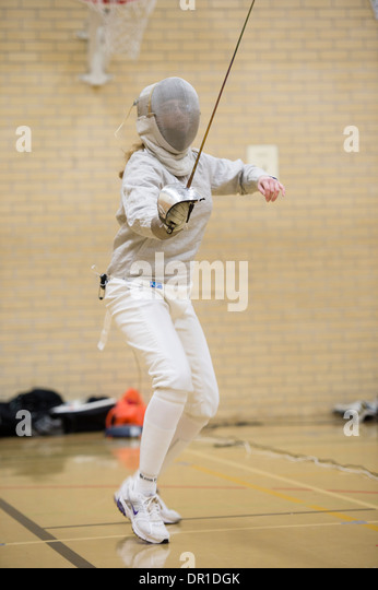 A woman Aberystwyth university student wearing safety mask competing at sabre style fencing, UK - Stock Image