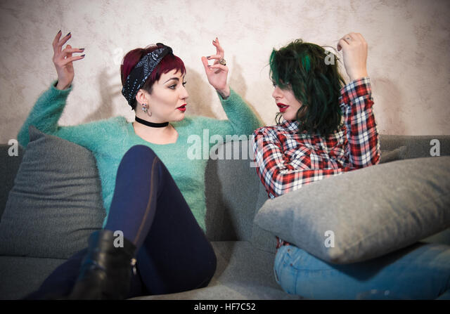 Young women couple friend at home talking hands up, discussion with emotive involvement - Stock Image