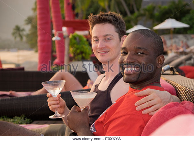Gay couple drinking together on urban rooftop - Stock Image