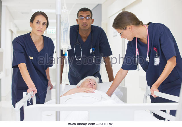 Emergency Medical Team Wheeling Patient Along Hospital Corridor - Stock-Bilder