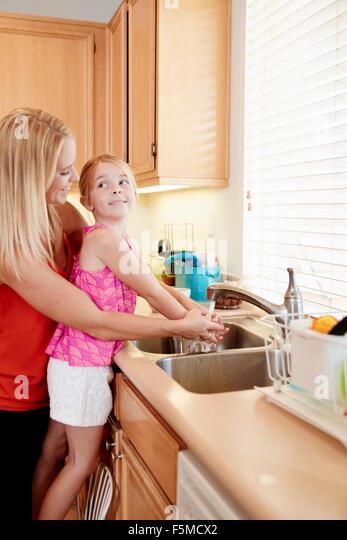 Mother washing daughter's hands in kitchen sink - Stock-Bilder