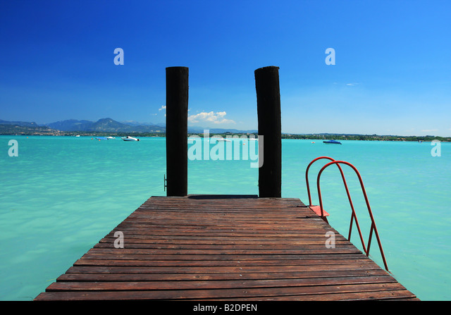 a small jetty in lake Garda Italy fantastic colors in sky and water Perfect for any sort of concept of vacations - Stock Image