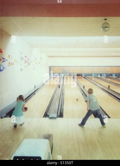 Two children bowling. - Stock Image