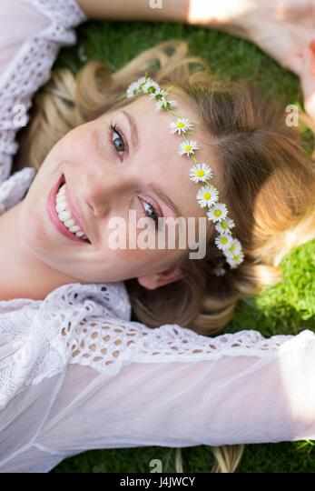 MODEL RELEASED. Young woman lying on grass wearing daisy chain. - Stock-Bilder