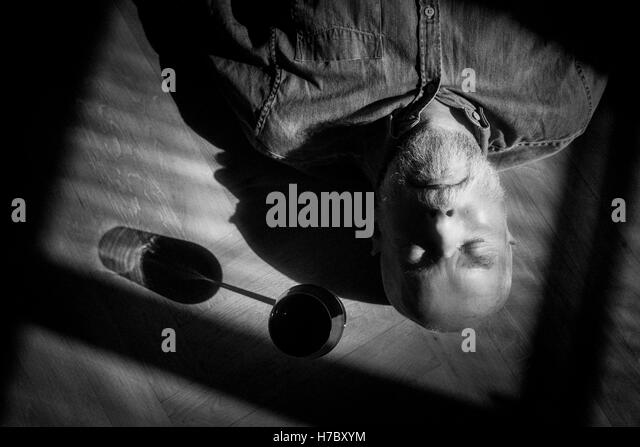 Old man resting on floor. Black and white portrait with deep shadows. Conceptual image of loneliness and retirement. - Stock-Bilder