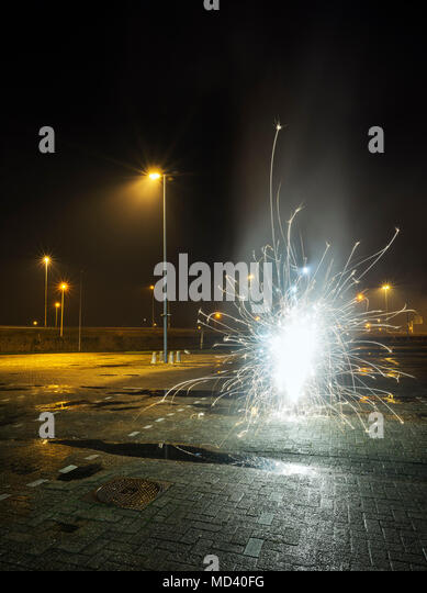 Fireworks going off in a car park, on new years eve, Heerenveen, Friesland, Netherlands - Stock Image