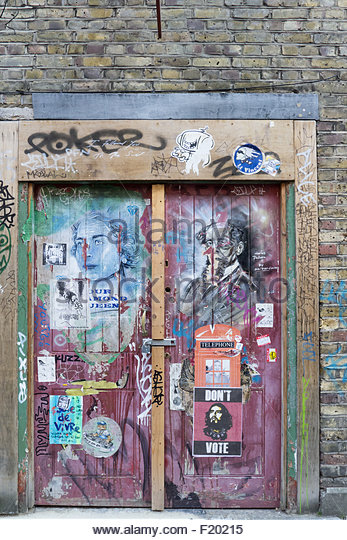 Spitalfields, London. artistic graffiti on a rough side door to a building with posters and tags; padlock, hasp. - Stock-Bilder