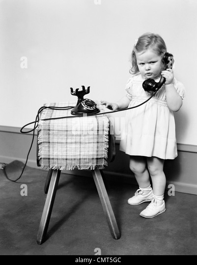 1930s 1940s UNHAPPY FROWNING LITTLE GIRL TALKING ON OLD BLACK ROTARY DIAL TELEPHONE - Stock Image