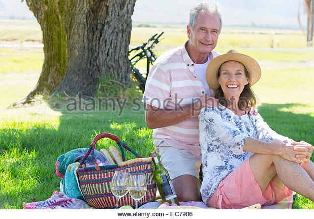 Senior couple sitting on picnic blanket - Stock-Bilder