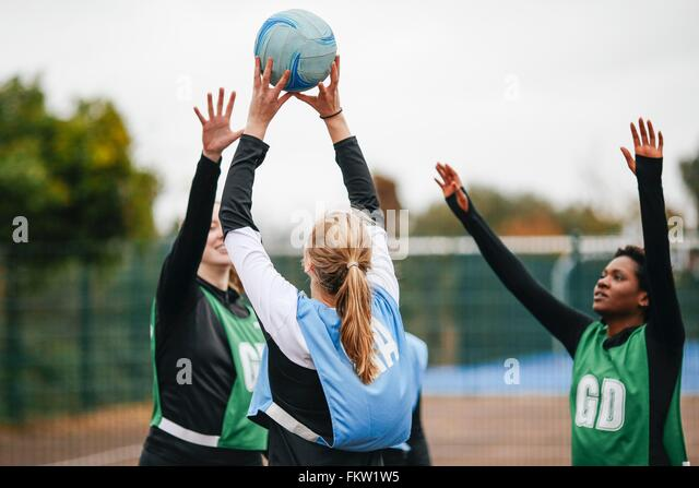 Female netball teams throwing ball on netball court - Stock Image
