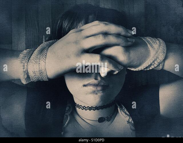 A girl with snake skin wrapped around her wrists and hands covering eyes. - Stock Image