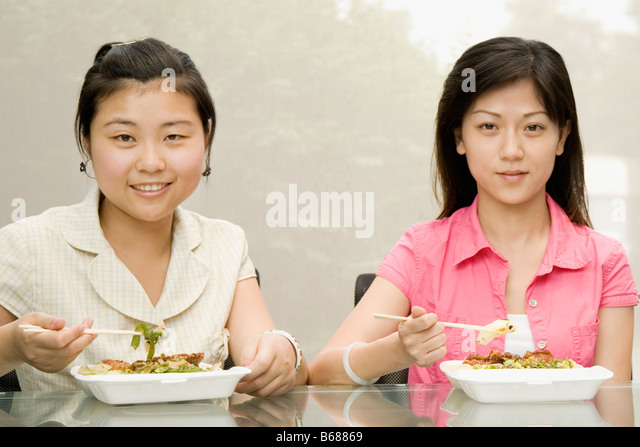 Portrait of two female office workers having lunch - Stock-Bilder