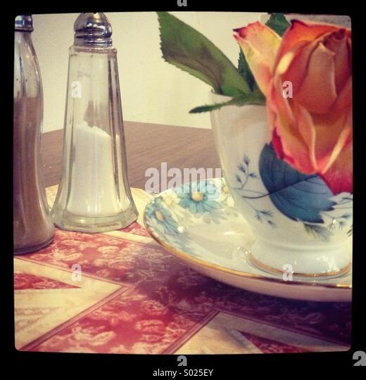 Rose, teacup and saucer, salt and pepper on Union Jack place mat. - Stock-Bilder