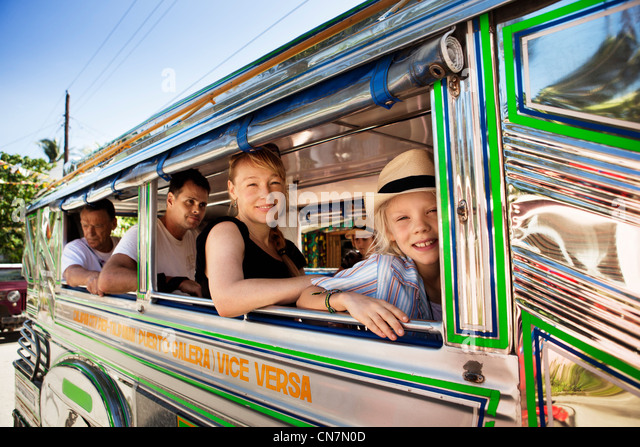 Passengers sitting by bus window - Stock Image