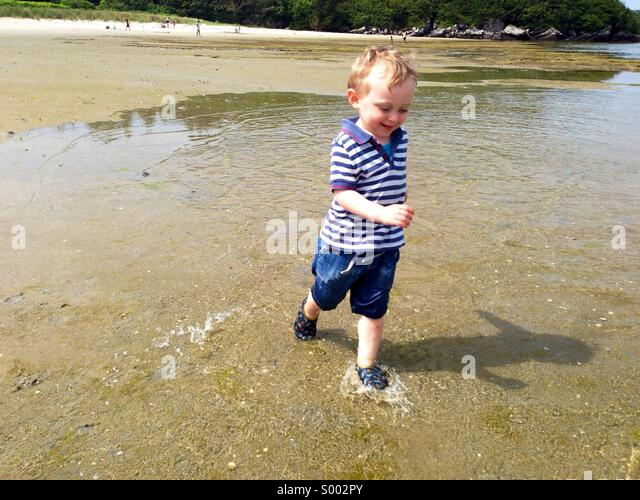 Young boy running in the water on a summers day - Stock Image