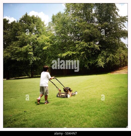 Boy mowing lawn - Stock Image