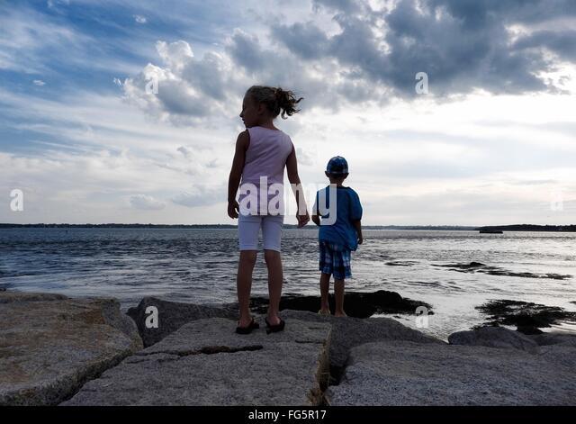 Rear View Of Siblings Standing On Rocks At Seaside Against Cloudy Sky - Stock Image