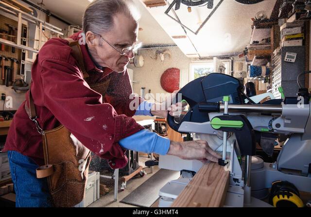 Senior man sawing woodblock in carpentry workshop - Stock Image