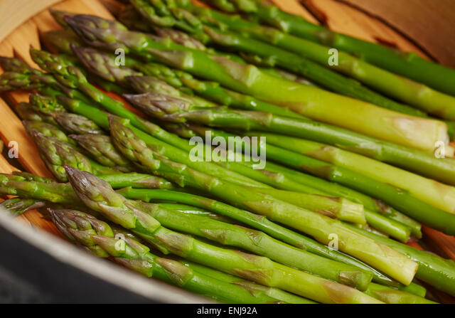 Asparagus steaming in a bamboo basket - Stock Image