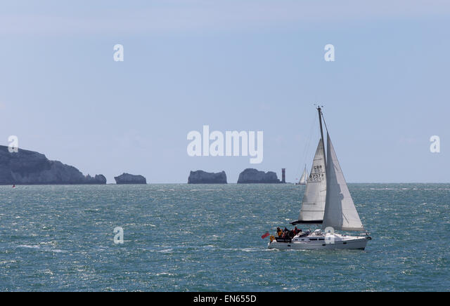 a yacht sailing past The Needles on the Isle of Wight - Stock Image