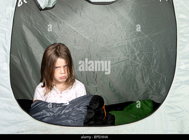 Shot of a Young Girl Looking Unhappy about Camping - Stock Image
