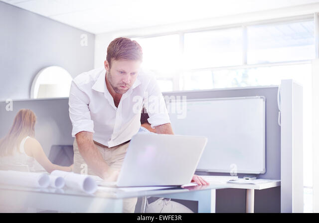 Architect using laptop in sunny office - Stock-Bilder