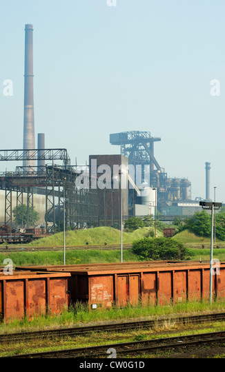Train running by steel factory - Stock Image