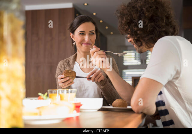 Mid adult couple having breakfast at dining table, Munich, Bavaria, Germany - Stock-Bilder