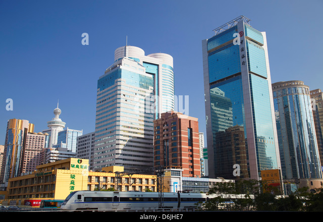 High speed train passing skyscrapers, Shenzhen, Guangdong, China, Asia - Stock Image