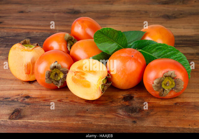 Persimmon. Kaki fruits on old wooden background. - Stock Image