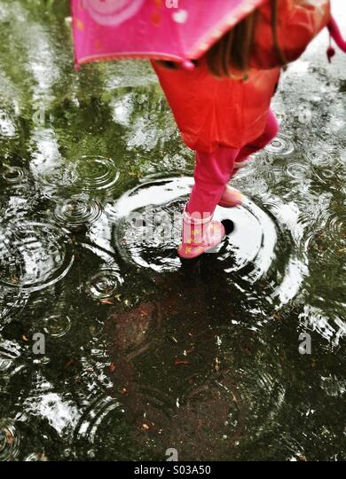 Child in red walking in the rain - Stock-Bilder