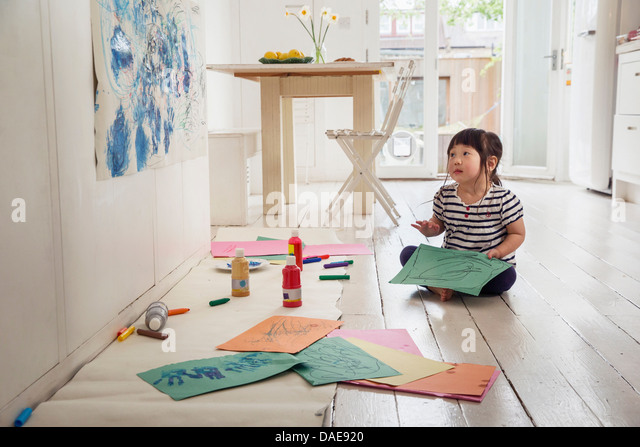 Female toddler sitting on floor with drawings - Stock-Bilder