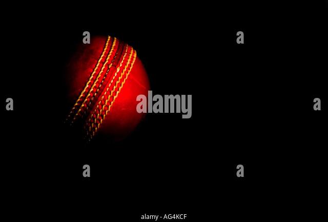 cricket ball emerging out of black background - Stock-Bilder