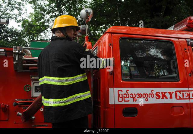 30.07.2013, Yangon, Republic of the Union of Myanmar, Asia - A fire fighter rushes to an emergency operation in - Stock Image