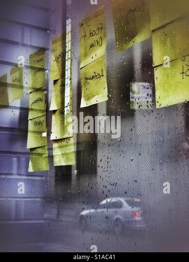 Post-It notes on an office window - Stock Image