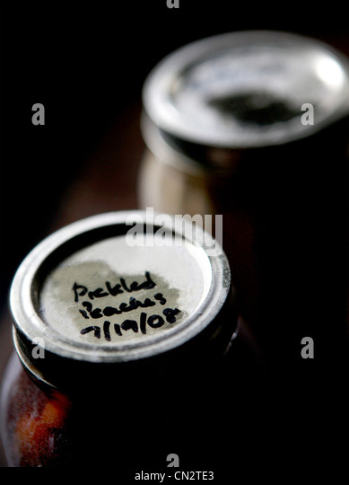 Jar of pickled peaches - Stock Image