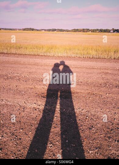 A shadow of a couple kissing beside a salt marsh on the coast of Connecticut, USA. - Stock-Bilder