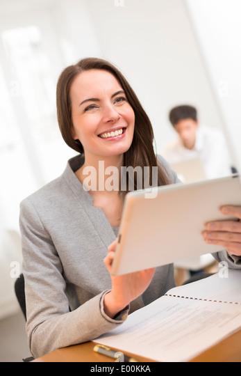 cute Female smiling desk tablet digital surfing web - Stock Image
