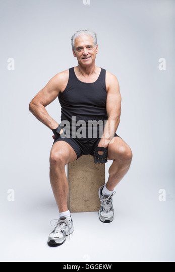 Senior man in sports clothing sitting in studio, portrait - Stock Image