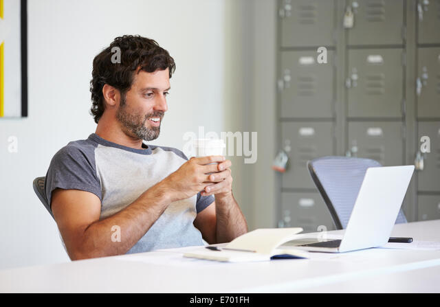 Casually Dressed Man Working In Design Studio - Stock Image